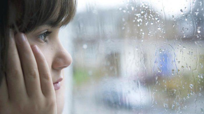 Perempuan sendirian menunggu di hujan